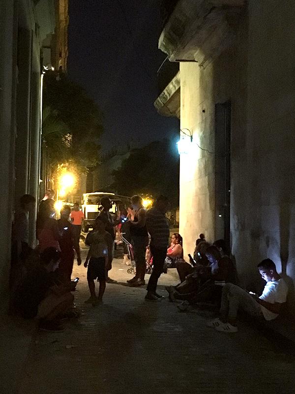 ホテル横の路地でWIFIを使う若者